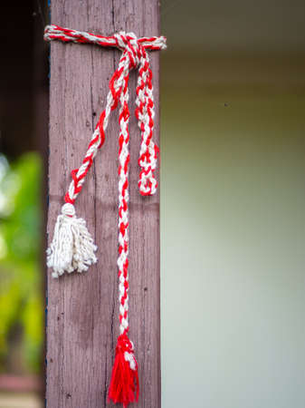 red and white knitting string tied up on house wooden pillar martisor romanian 1st of march celebration concept