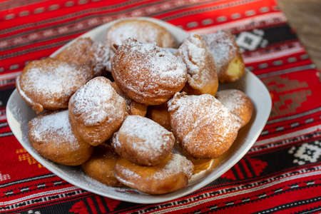 romanian mini doughnuts on a plate on red traditional cloth