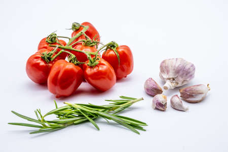 red cherry tomatoes with garlic cloves and rosemary on white background