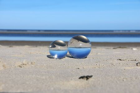 Two crystal balls lying in the sand at the beach Stock Photo