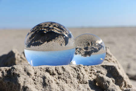 Two crystal balls are lying in the sand