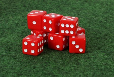 A heap of red dices are lying on a green ground