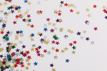 Heap of small colorful shiny stars in the white studio