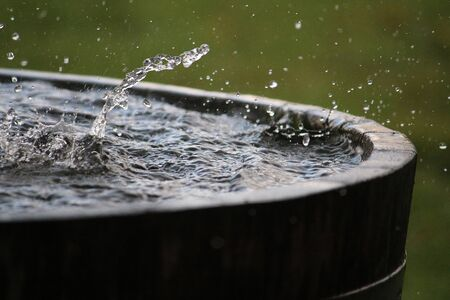 Rain is falling in a wooden barrel full of water in the garden Imagens