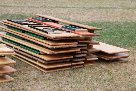 Stack of wooden party tables and benches are lying in the garden after a party Stock Photo