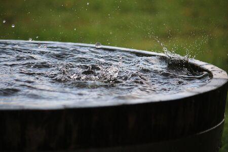 Rain is falling in a wooden barrel full of water in the garden Stock Photo