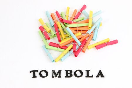 Heap of colorful tombola tickets in the white studio with a tombola letter in the front with wooden letters Archivio Fotografico