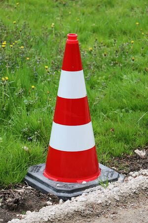 Striped pylon is standing at the side of the street