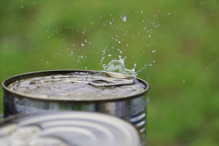 Rain is splashing on the top of a metallic can outdoor