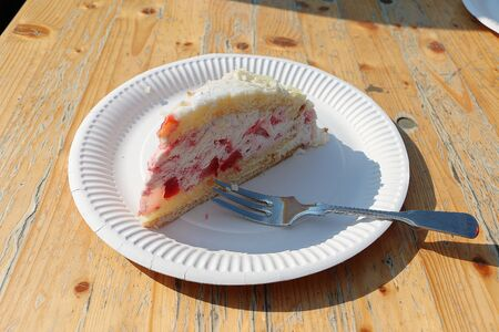 Close up of a delicious strawberry cheesecake on a plate with a fork in the wooden table Stockfoto