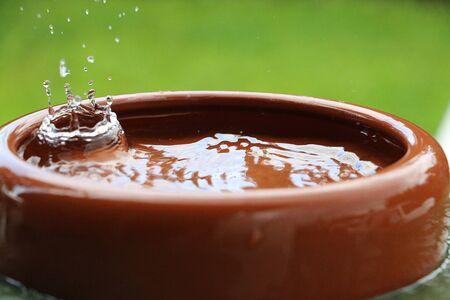 Rain is falling in a ceramic bowl full of water Stock Photo