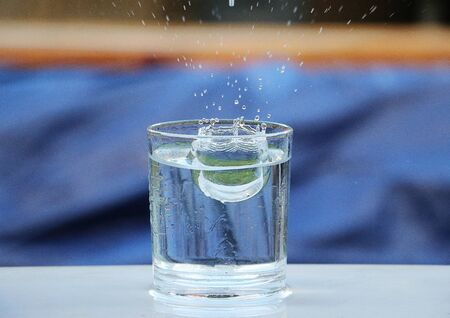 Raindrops are falling into a glass on the table 版權商用圖片