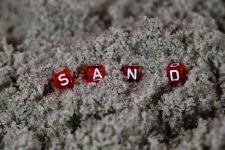 Close up of small red dices with white letters in the beach sand writing the word sand