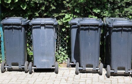 Some dark rubbish bins stood in a row at the fence waiting for the pickup