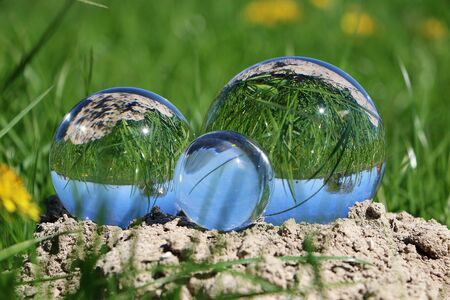 Three differently sized glass balls lie on a chair in the garden and reflect the nature