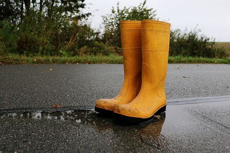 A pair of yellow rubber boots standing in a puddle on a rainy day Reklamní fotografie