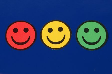 Three cut out traffic lights colored smileys lying on a blue background in the studio
