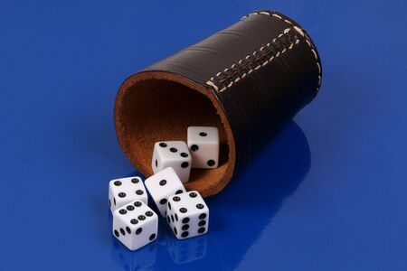White dice falling from a recumbent leather cup on a blue background
