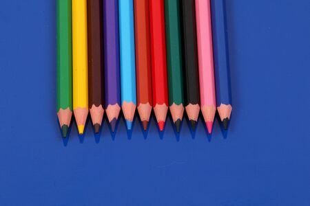 Different colored crayons lying in a row on a blue background 版權商用圖片