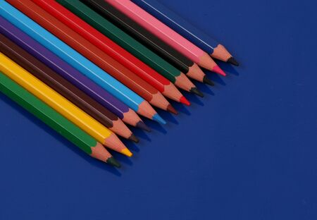 Different colored crayons lying in a row on a blue background Stok Fotoğraf - 135051302
