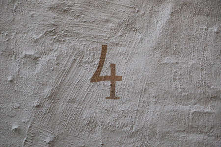 Painted number four at a white house wall