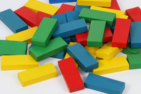 Heap of colorful wooden building blocks are lying in a white studio 版權商用圖片