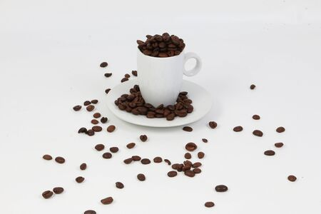 Coffee beans in a small mug on a small plate in white studio Stok Fotoğraf - 135248902