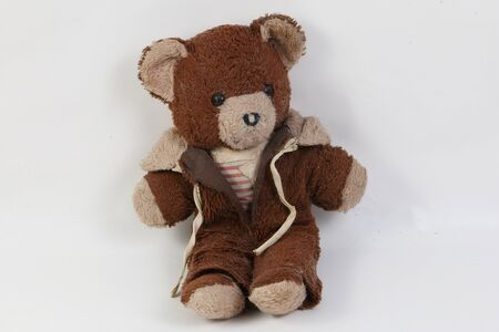 Old brown damaged teddy bear is sitting in the white studio Stok Fotoğraf