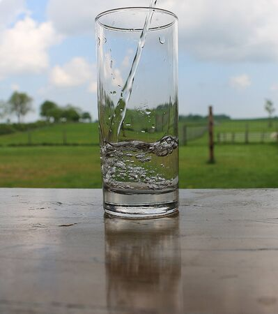 Fresh water falls into a glass which stands on a table in the garden Stockfoto