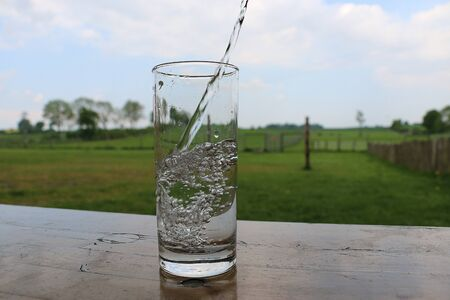 Fresh water falls into a glass which stands on a table in the garden 版權商用圖片