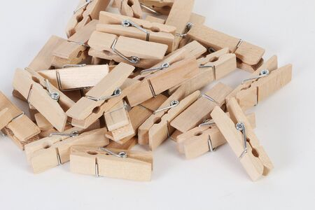 Heap of small wooden clothespins on a white backround