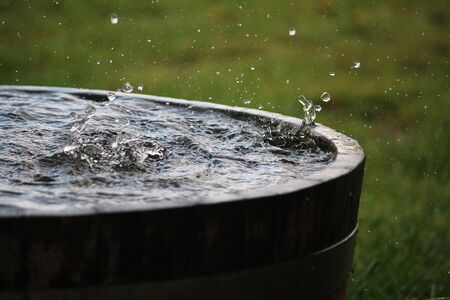 Rain is falling in a wooden barrel full of water in the garden Standard-Bild