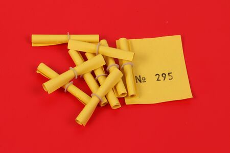 Yellow raffle tickets with a winning number are lying on a red ground in the studio Archivio Fotografico