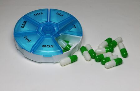 Weekly pillbox with green white capsules