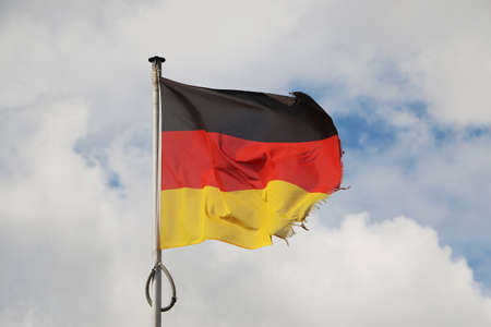 Waving Germany flag on a pole with cloudy sky