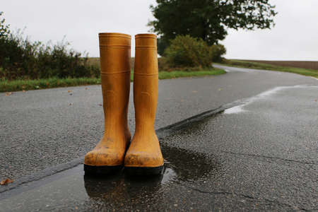 A pair of yellow rubber boots stand in a puddle on the street on a rainy day Stock Photo