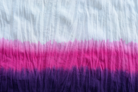 colourful tie: tie dye pattern dip dyed technique on cotton fabric background. Stock Photo