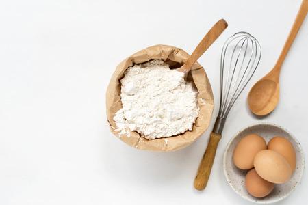 eggs and flour on white table background. basic baking background.