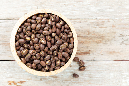 roasted peaberry coffee bean in bowl on wooden background.