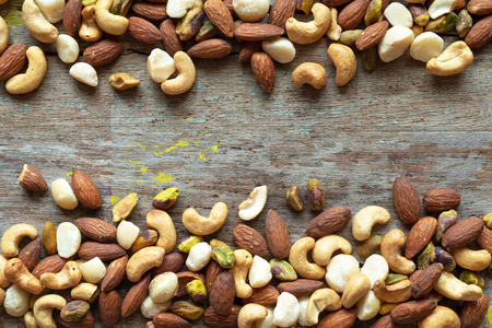 cashews, almonds pistachios, macadamia, mixed nuts healthy snack frame on wooden background Stock Photo