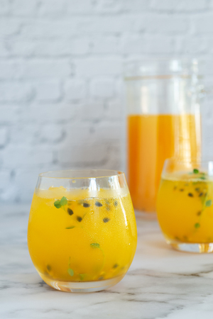 glass of passion fruit juice on marble table