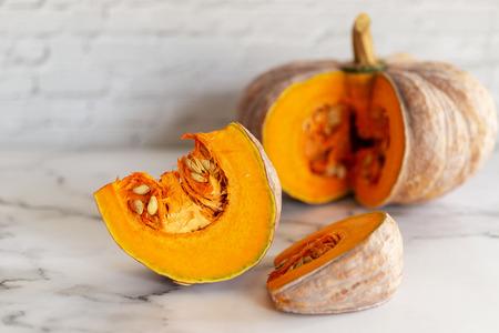 sliced raw pumpkin on marblel table background.