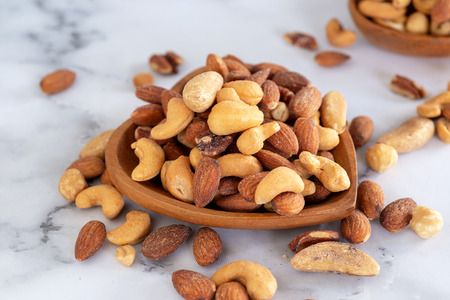 roasted mixed nuts in wooden bowl on barble table background.