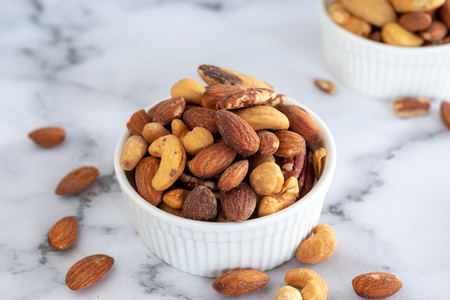 roasted mixed nuts in white ceramic bowl on barble table background. Stok Fotoğraf