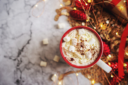 cup of hot cocoa or chocolate with Christmas present on white marble table from above