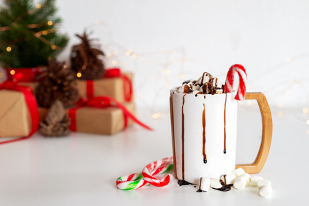 a cup of hot cocoa or chocolate with Christmas present on white table Stok Fotoğraf