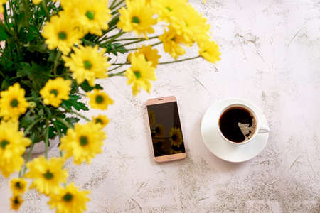 A cup of black coffee with smartphone and yellow flowers.