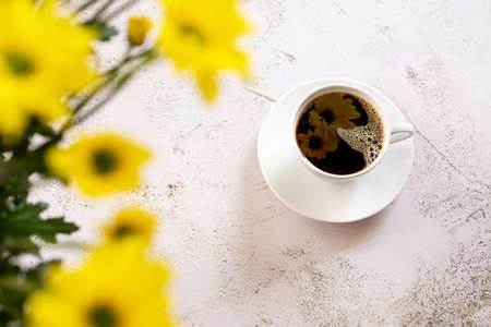 A cup of hot coffee on the table with yellow flowers.