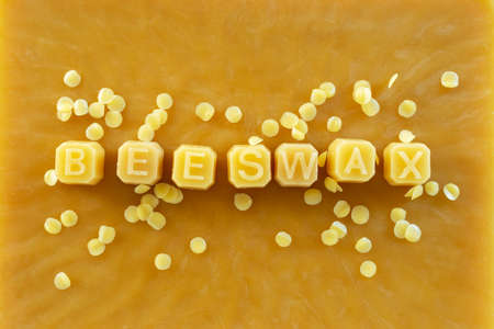 beeswax letters made from yellow natural beeswax on  beeswax texture background.