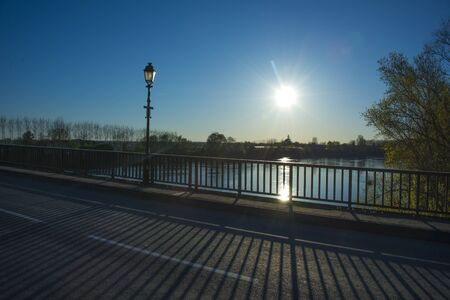 billow: Sunset over the river Garonne in the background of the bridge and trees